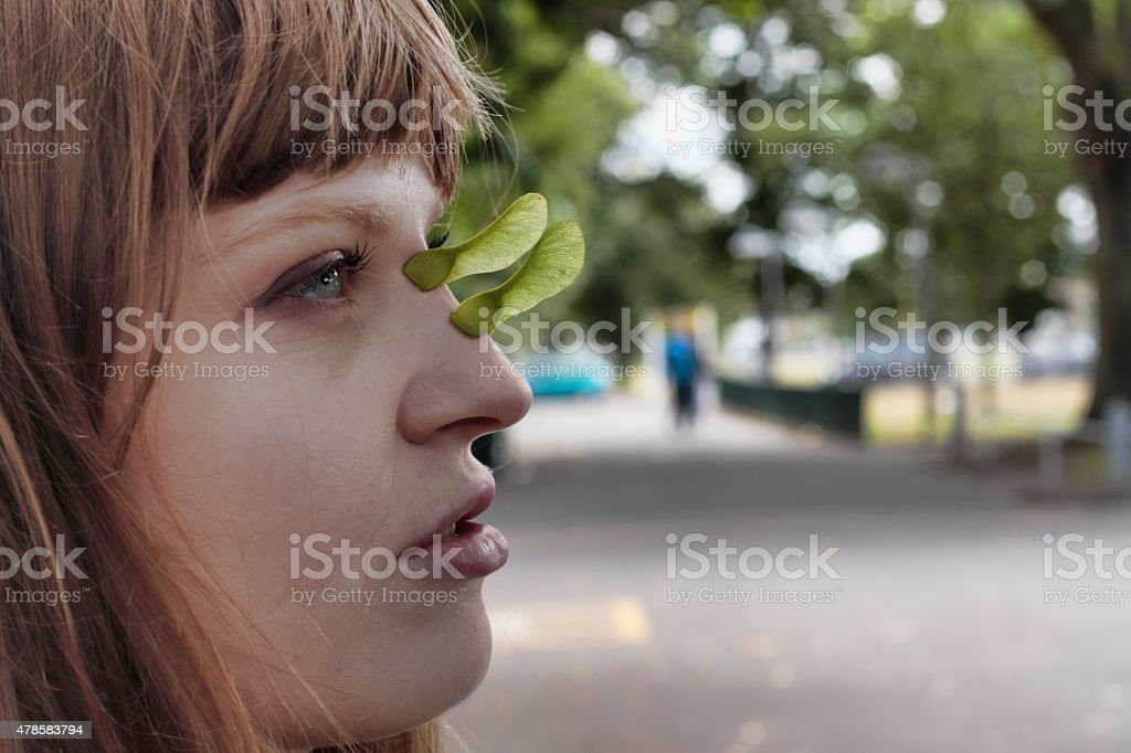 Latvian outdoor rhino girl displaying two maple seed horns stock photo