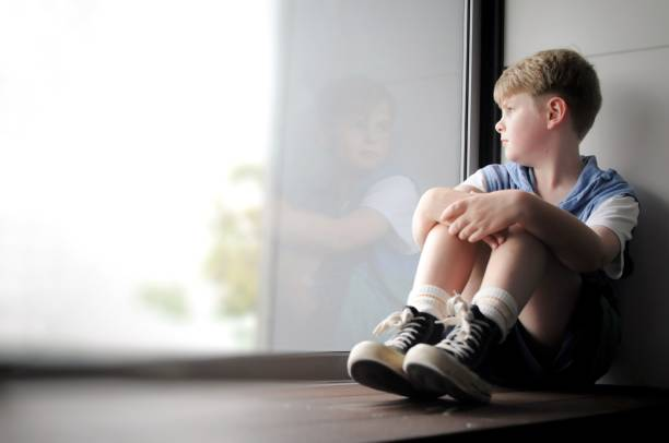 childhood pondering - boy looking out window stock pictures, royalty-free photos & images