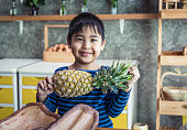 Asian childhood student holding a pineapple