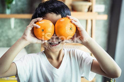 Asian childhood student holding an oranges
