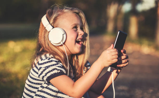 Childhood time. Cute little girl listening to music with mobile phone and headphones stock photo