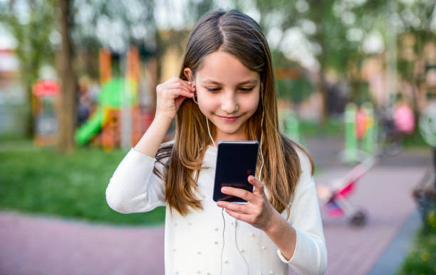 Childhood time. Cute little girl listening to music with mobile phone and headphones. Lifestyle concept stock photo