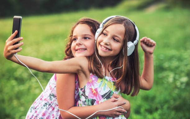 Childhood time. Two little girls making a selfie with mobile phone stock photo