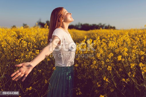 Beautiful smiling redhead enjoying a carefree summer day in a yellow flower field.