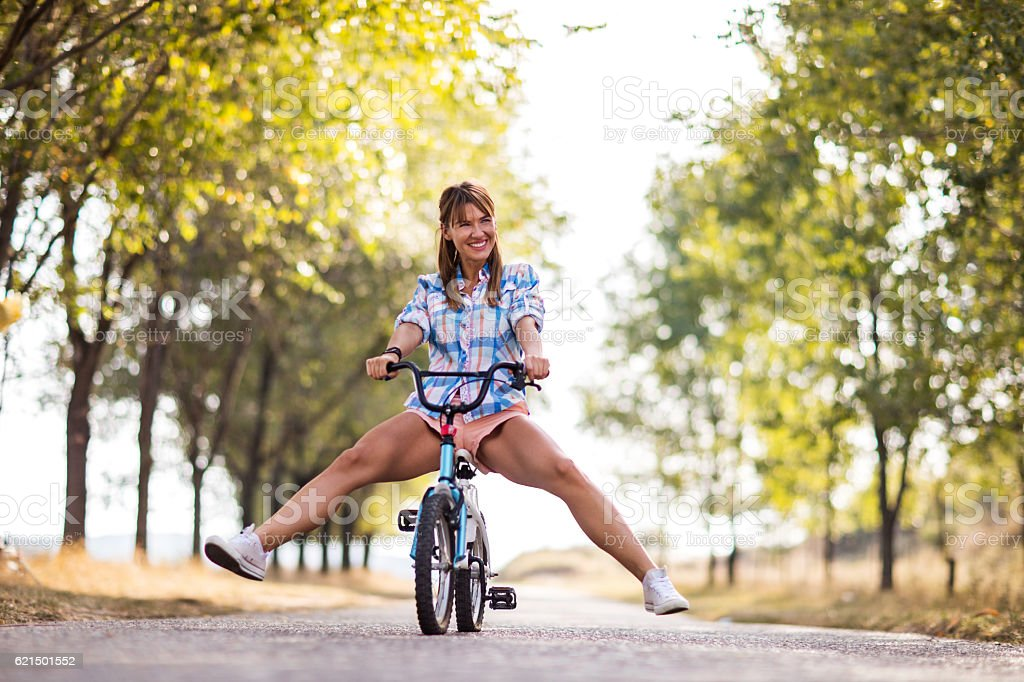 Childish woman riding small bicycle at the park. Lizenzfreies stock-foto
