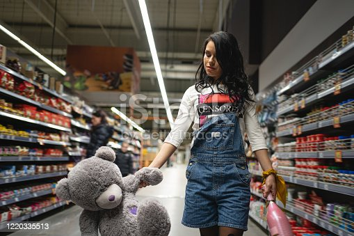 926078666 istock photo Childish young woman holding a teddy bear and bottle of champagne in the supermarket 1220335513