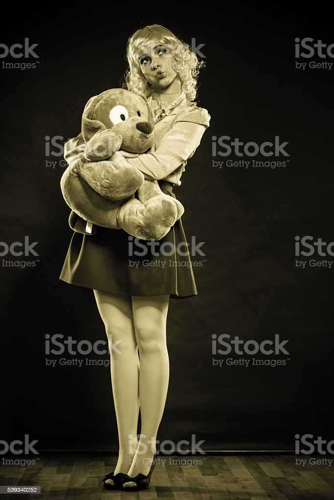 Childlike Woman With Dog Toy On Black Stock Photo - Download