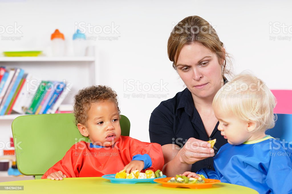 Childminder/ Carer Feeding Toddler While His Peers Watches royalty-free stock photo