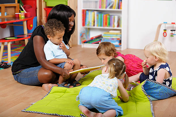 Childminder/Carer Reading To A Group Of Toddlers At Nursery stock photo