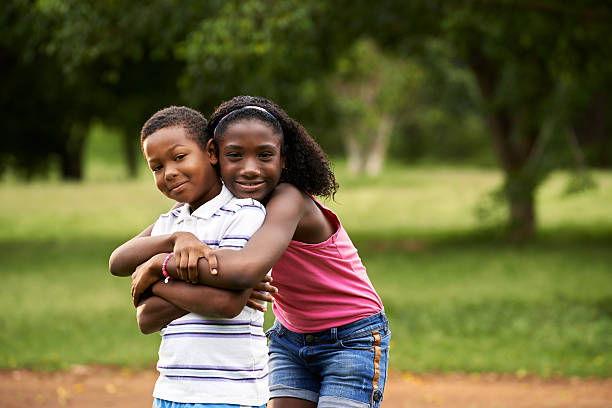 children african boy and girl in love hugging People in love with happy little black girl and boy hugging and embracing in city park cute teen couple stock pictures, royalty-free photos & images