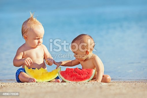 istock Children after swimming have fun and eat fruits on beach 489075506