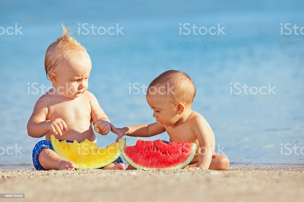 Children after swimming have fun and eat fruits on beach stock photo