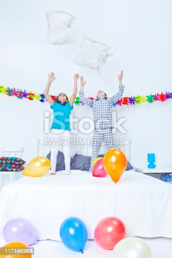 Boy and girl playing with balloons and cushions in a bedroom party.