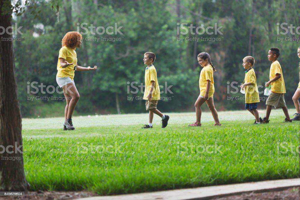 Enfants et conseiller au camp d'été dans le parc - Photo