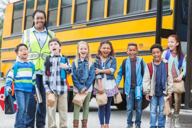 Children and crossing guard standing outside school bus stock photo