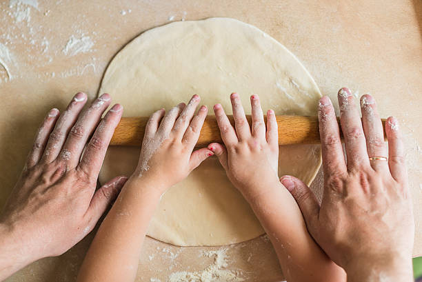 Children and dad hands rolled dough stock photo