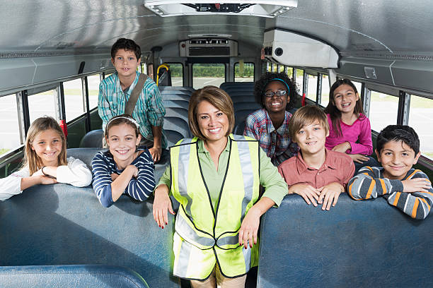 Children and driver inside school bus stock photo