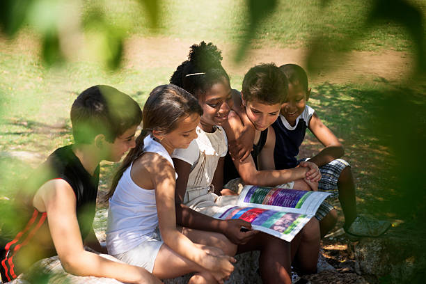 Children and education, kids reading book in park stock photo