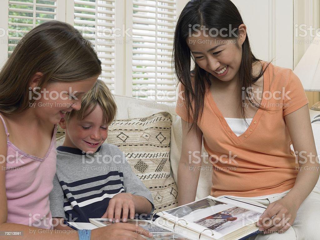 Crianças e Bolsa estudante olhando para Álbum de Fotografia foto de stock royalty-free