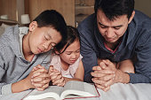 istock children and father parent praying with bible on the bed, family pray together, online church, home church 1308346191