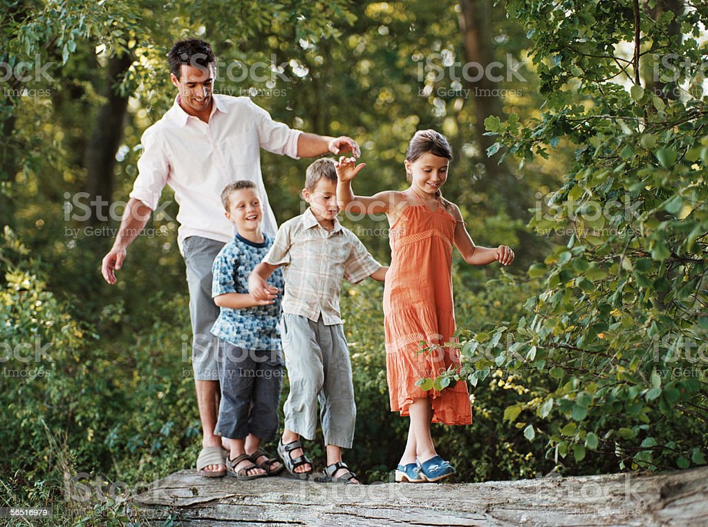 Children and father walking on a log royalty-free stock photo