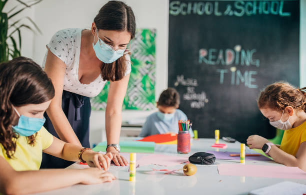Children and female teacher on class in private school classroom