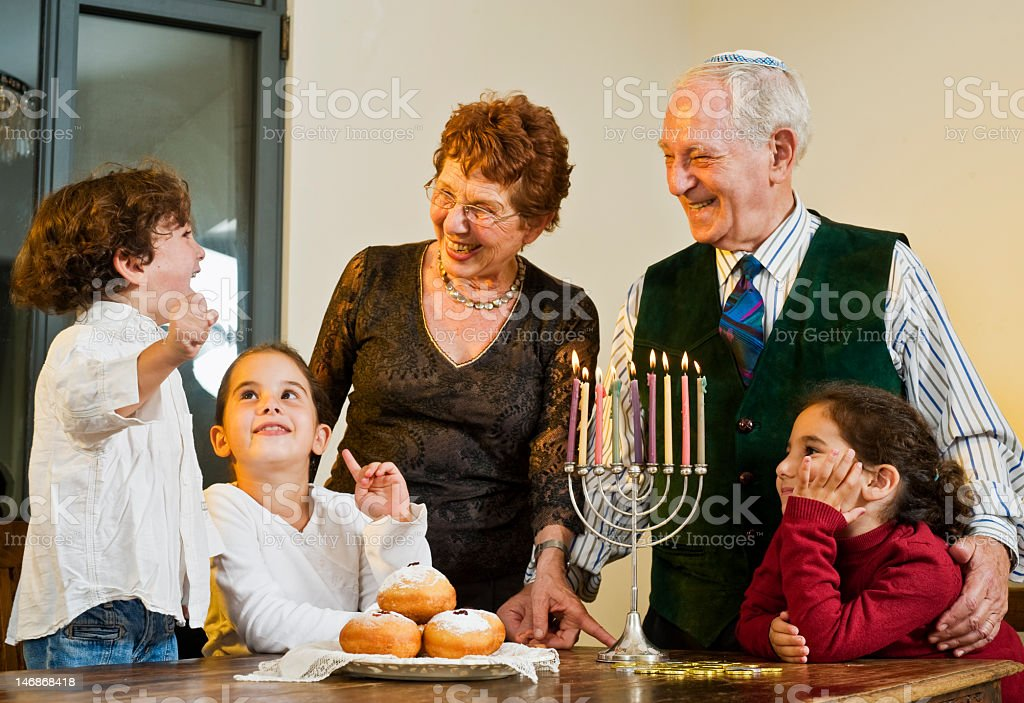 Children and grandparents around the table for Hanukkah stock photo