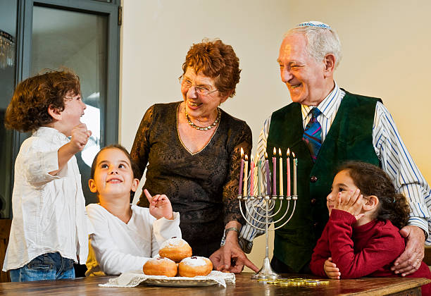 Children and grandparents around the table for Hanukkah grandperents and grandchildren lightening Hanukkiyah together judaism stock pictures, royalty-free photos & images
