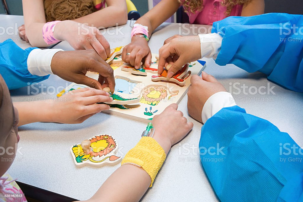 Children and nurses playing with puzzle stock photo