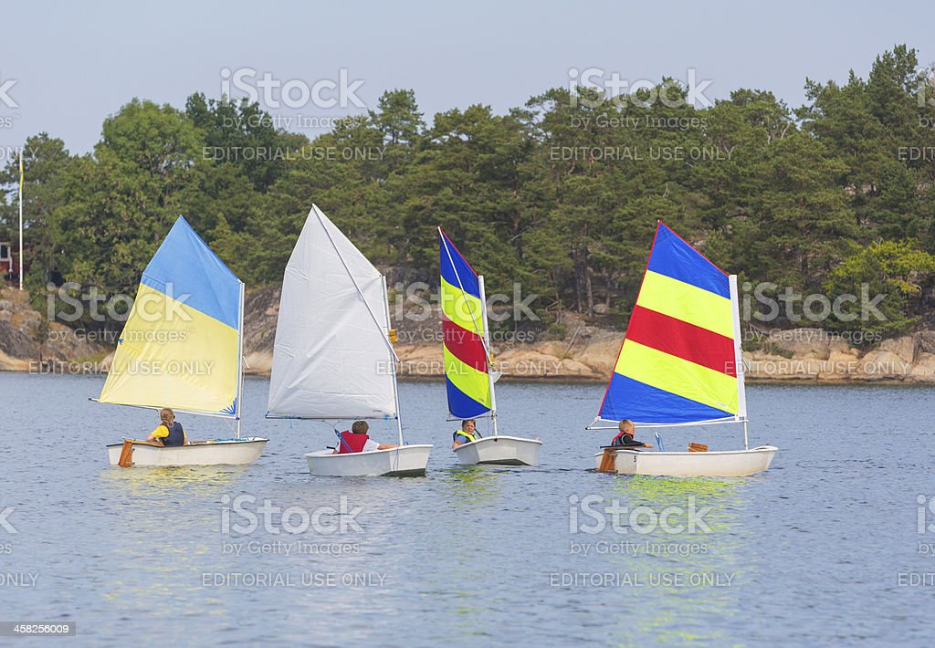 Children and optimist dinghies with colorful sails in Stockholm Archipelago royalty-free stock photo