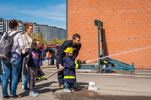 Children and parents at a fire station trying a fire hose.