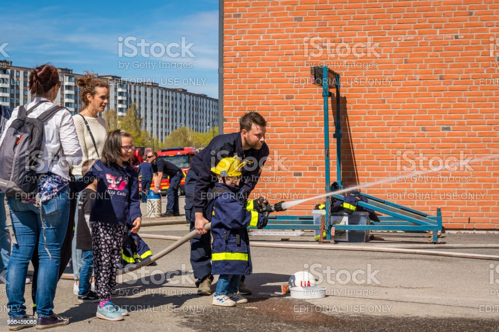 Children and parents at a fire station trying a fire hose. stock photo