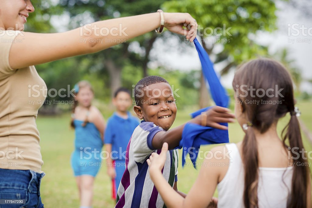 Children and teacher playing games in city park stock photo