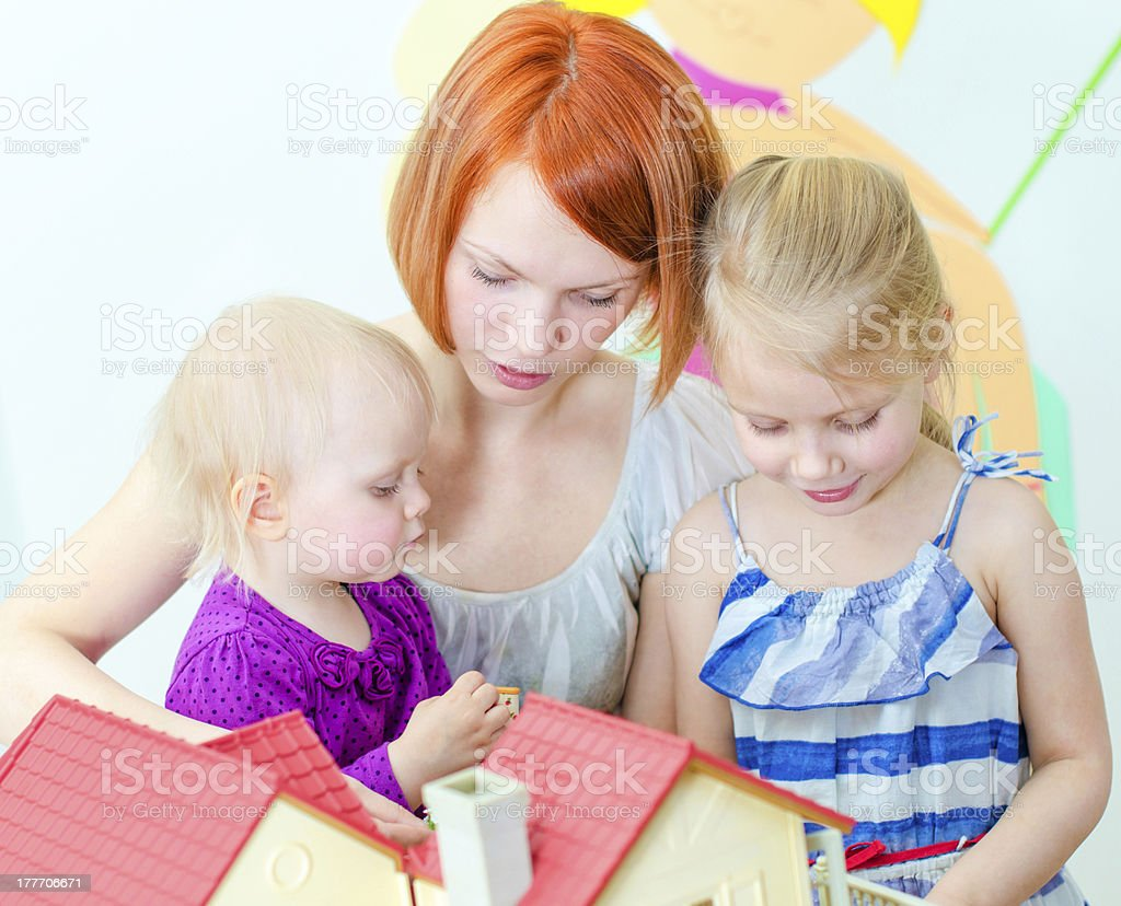 Children and their mother playing with dollhouse stock photo