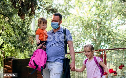 Father and children going to preschool during coronavirus. Surgical mask for illness prevention.