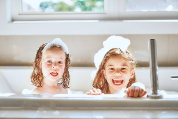 children are bathing in a bath Happy children girls are bathing in a bath with foam and bubbles. bathtub stock pictures, royalty-free photos & images