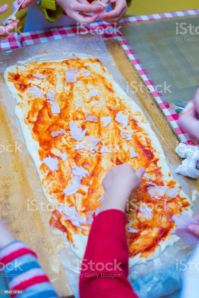 children are cooking pizza. hands in the frame royalty-free stock photo