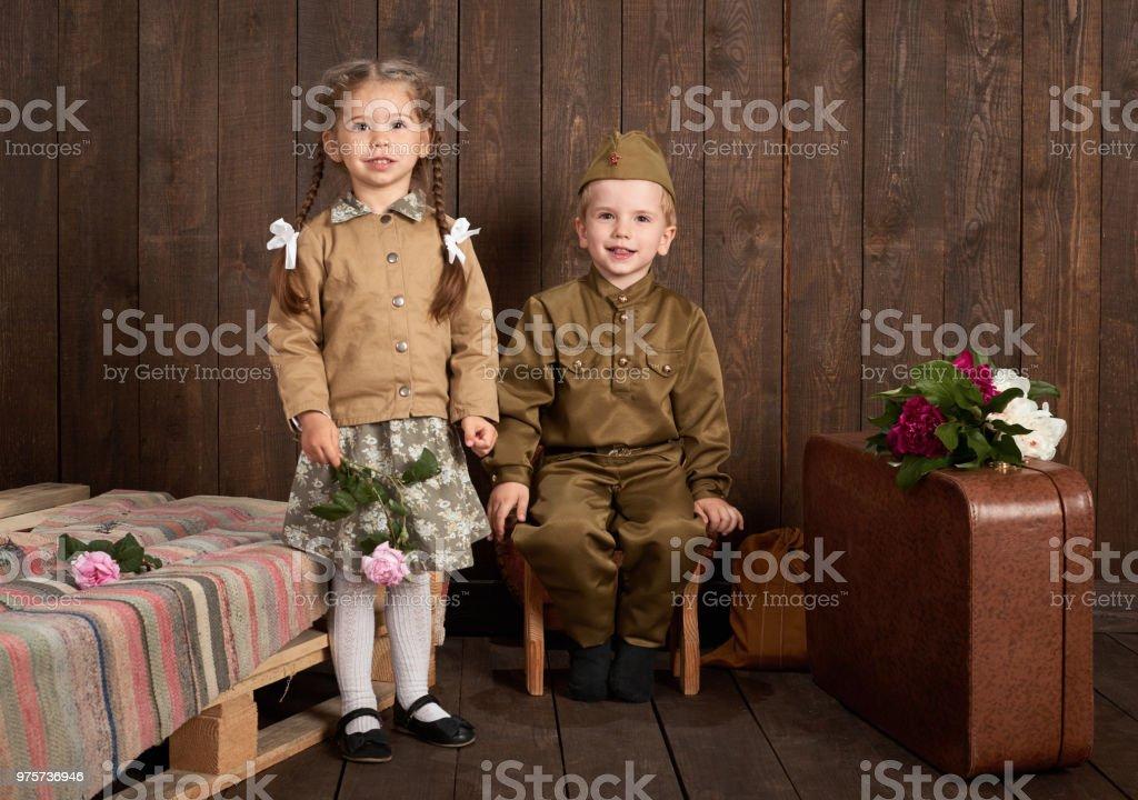 Kinder sind im Retro-Militäruniformen senden ein Soldat in der Armee, dunklem Holz, Retro-Stil gekleidet. - Lizenzfrei Altertümlich Stock-Foto