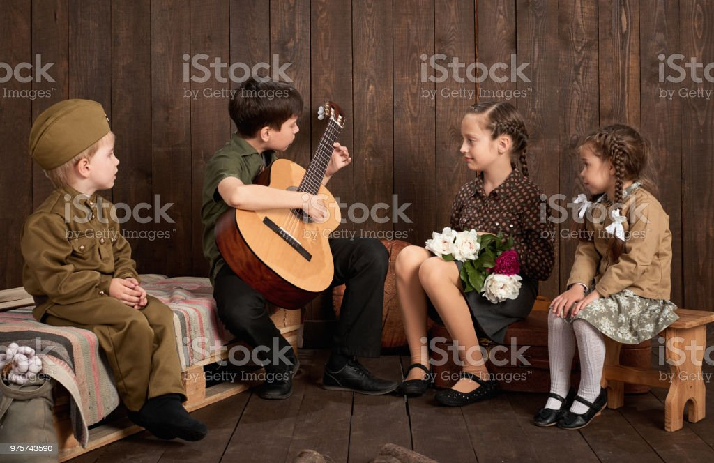 Kinder sind im Retro-Militäruniformen sitzen und spielen Gitarre, gekleidet senden ein Soldat in der Armee, dunklem Holz, Retro-Stil - Lizenzfrei Altertümlich Stock-Foto