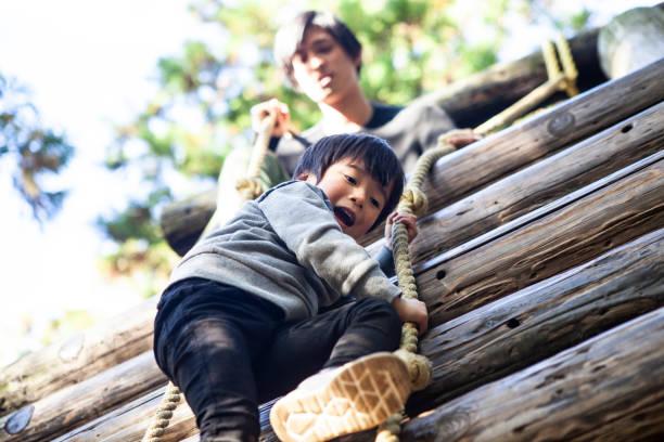 kinderen genieten van atletische speeltoestellen. - bos spelen stockfoto's en -beelden