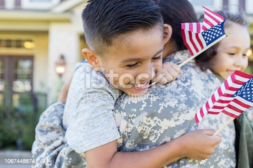 Smiling little boy and girl give their soldier mom a big hug on her return home from service. The children are holding small US flags.