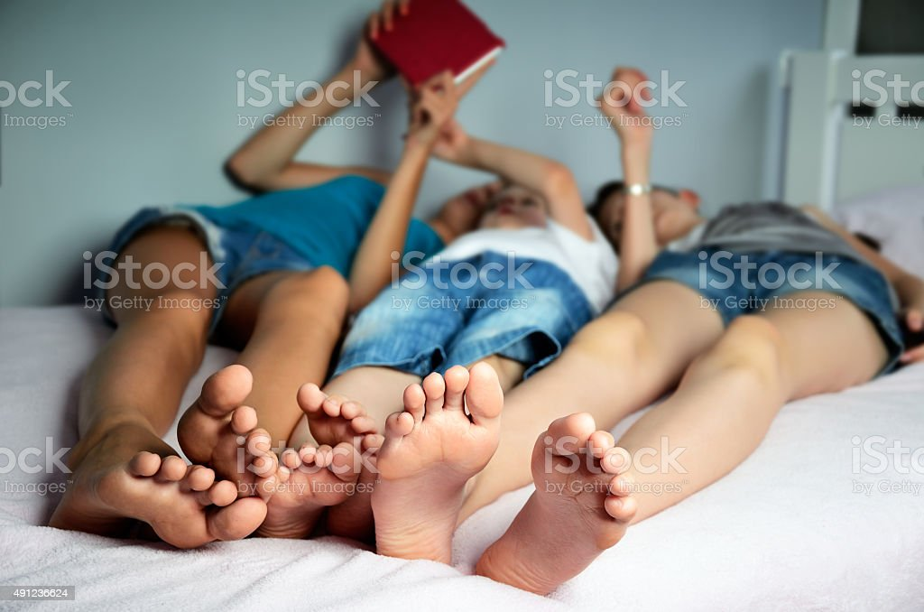children are lying on the bed and play in tablet stock photo
