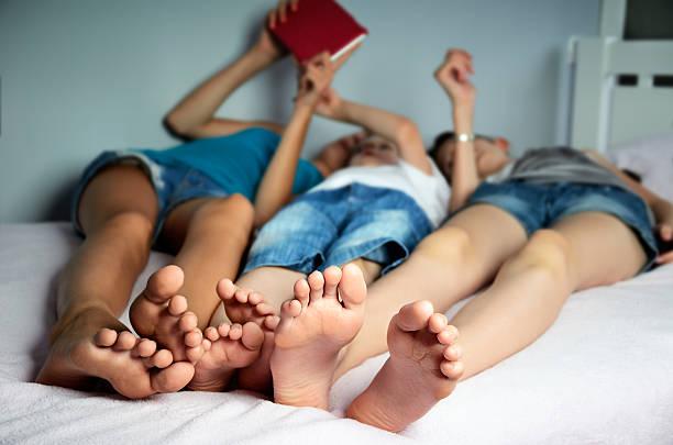 Los niños son yacer en la cama y juegue en el comprimido - foto de stock