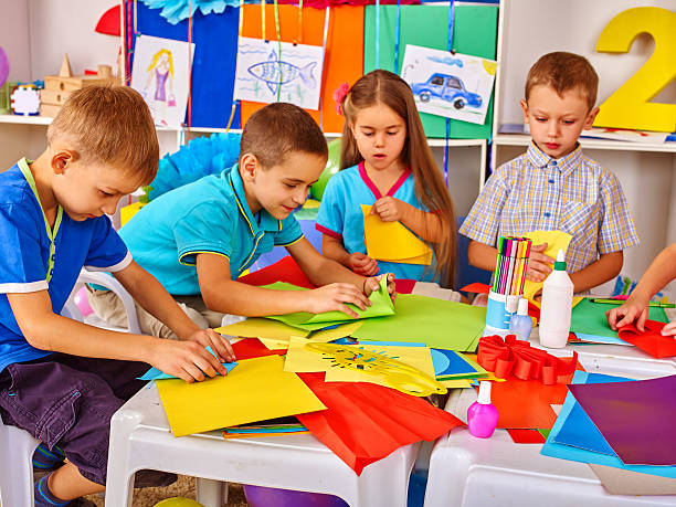 Children are making something out of colored paper. – Foto