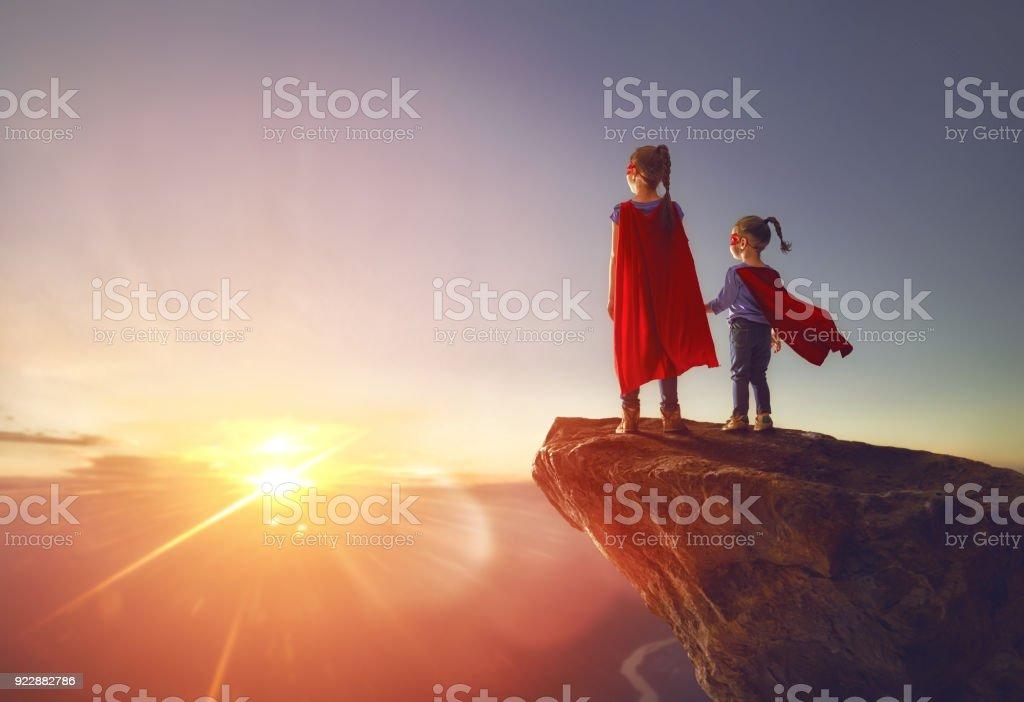 children are playing superhero stock photo