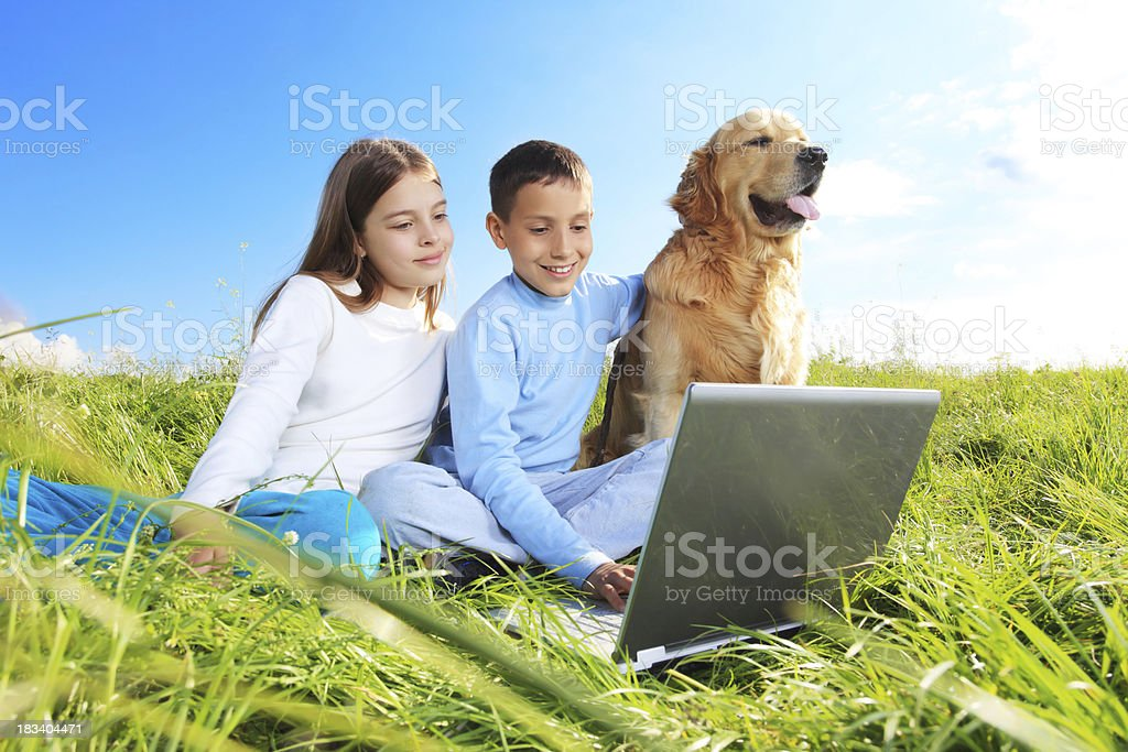 Children are playing with laptop and a dog. royalty-free stock photo