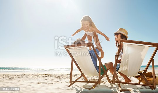 Shot of a man sitting on the beach with his family while lifting his daugther to the skyhttp://195.154.178.81/DATA/i_collage/pu/shoots/784349.jpg