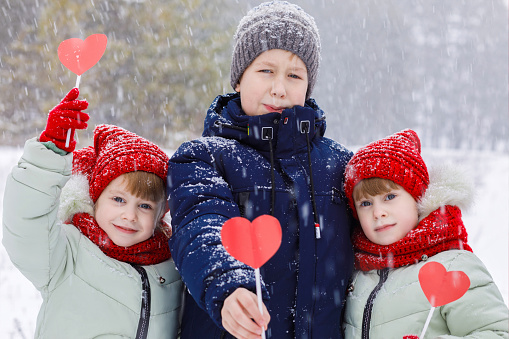 Smiling little girl twins are standing near their brother in the winter park and holding the sticks with paper hearts at the falling snowflakes background. The concept is St Vslentine day celebration.