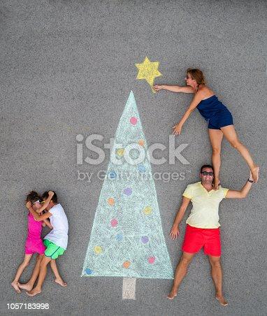 istock children argueing besides christmas tree, parents decorating 1057183998