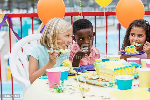 A group of three multi-ethnic children at a birthday party sitting at a table eating cake.  They are 7 and 8 years old.